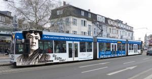 """Mit der Aufschrift """"Die Waffen nieder!"""" fährt die Bertha-Bahn noch bis September 2020 durch Bonn."""